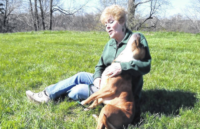 Friends of the Highland County Dog Pound Treasurer Pat Lawrence sits with Chevy, a dog who has since been adopted from the pound.