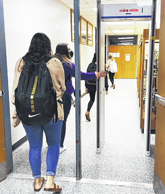 McClain High School students pass through a metal detector that takes their temperature.