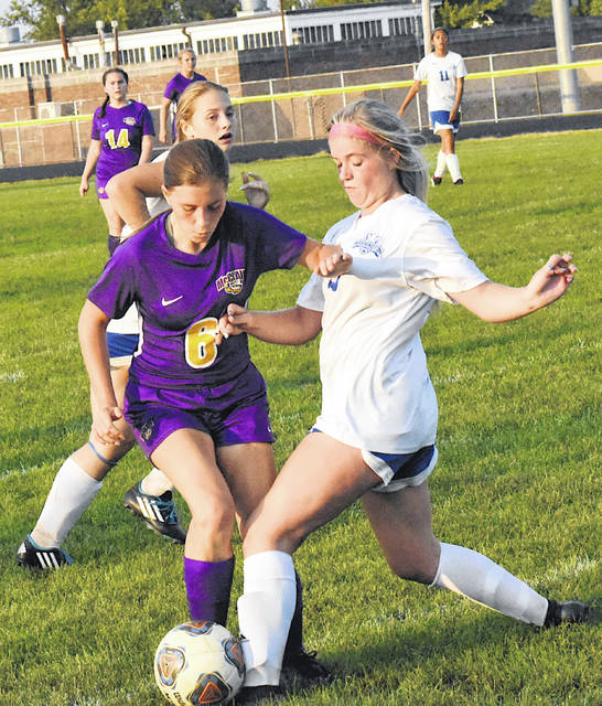 Lady Tiger footballer Kaitlyn Jett attempts to dribble past a Washington Lady Blue Lions defender in the second half of McClain's 7-1 Frontier Athletic Conference girls soccer win on Thursday in Greenfield.