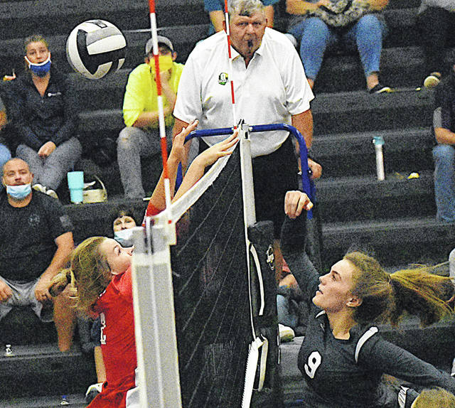 Hillsboro's Emma Birkhimer (left) and Lynchburg-Clay's Lainie Lunsford meet at the net Wednesday at Lynchburg-Clay High School where the Lady Mustangs hosted the Lady Indians in a cross-county volleyball matchup.