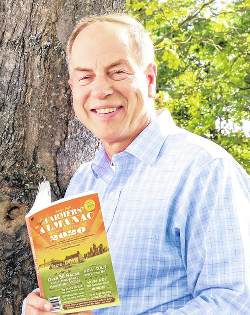 Farmers' Almanac Editor Peter Geiger holds a copy of the magazine's 204th edition.