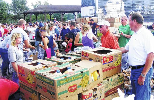 """<p class=""""p1"""">In a scene from the 2012 Help the Hungry event, Bill Bowman, right, and volunteers and participants give away food at Liberty Park in Hillsboro, the event's former location. This year's Help the Hungry event will be held at New Life Ministries on Friday, Sept. 18 from 1-5 p.m."""