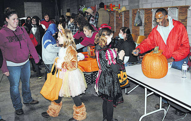 Despite damp and dreary weather, hundreds of children and adults turned out for the annual Boo Fest event Thursday sponsored by WSRW and WCHO. It was held inside the former fire station in uptown Hillsboro. In this picture, Richard Burns (far right) with the Hillsboro City Schools hands a treat to Miley Messer, a Hillsboro elementary student. Pictured to Miley's left is Brianna Messer. Most of the county cancelled trick or treat activities Thursday due to the weather. The communities of Greenfield, Hillsboro and Leesburg will all hold trick or treat Saturday. Greenfield's is from 6-8 p.m., and Hillsboro's and Leesburg's are from 5-7 p.m.