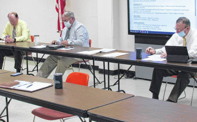 Commissioners (from left) David Daniels, Jeff Duncan and Terry Britton attend to county business during Wednesday's meeting.