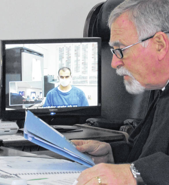 In a video conference call held Monday afternoon in Highland County Common Pleas Court, Nickolaus Garrison entered a not-guilty plea to new charges of escape and assault on a peace officer. Visiting judge Daniel Hogan (right) presided over Monday's arraignment hearing. Garrison is shown on the video screen.