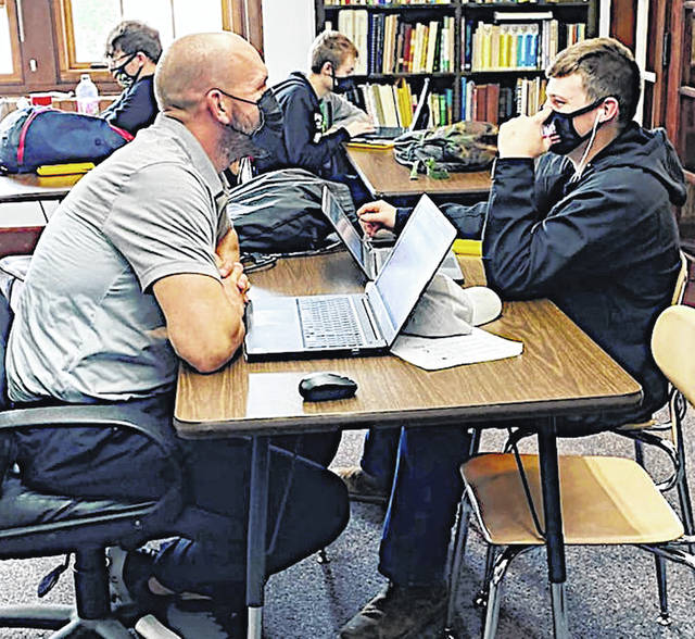 New McClain High School teacher Mark Bihl (left) talks with a student Devin Hall.