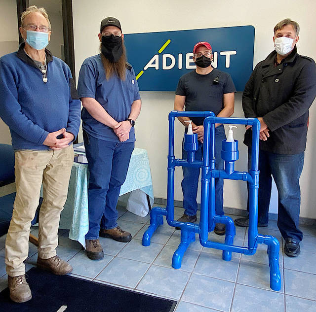 Greenfield Council Chairman Phil Clyburn (far left) and Greenfield City Manager Todd Wilkin (far right) are pictured with (l-r) Steven Hintze, a controls engineer at Adient, and Tim Pence, maintenance supervisor, on Friday as the city officials accepted sanitizing stations made for the village at Adient.