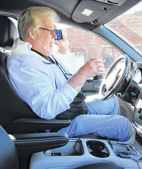 Demonstrating talking on a cell phone and drinking coffee while steering with his knee, and at the same time not wearing his seat belt, local businessman and radio broadcaster Herb Day shows what not to do behind the wheel of a vehicle for Distracted Driving Awareness Month.