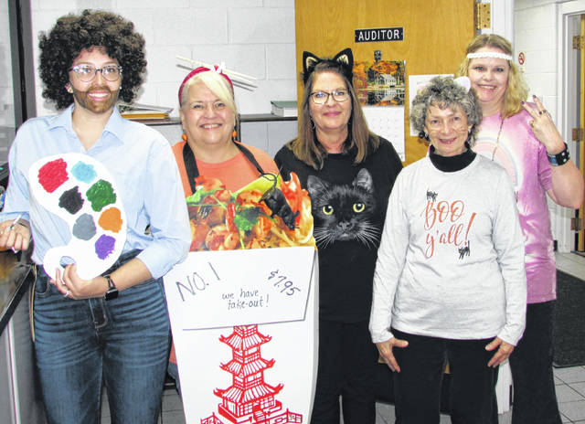 "The Highland County Auditor's Office got into the Halloween swing of things with these ladies helping Bill Fawley take care of county business Wednesday. Shown, from left, are artist Bob Ross (Andrea Purcell), Debbie Zile dressed as a Chinese restaurant take out item, Sue Young as a black cat, sporting a Southern-cat touch in her ""Boo, Y'all"" shirt was Susan Price, and in costume as a 1960s flower child was Melanie Anderson."