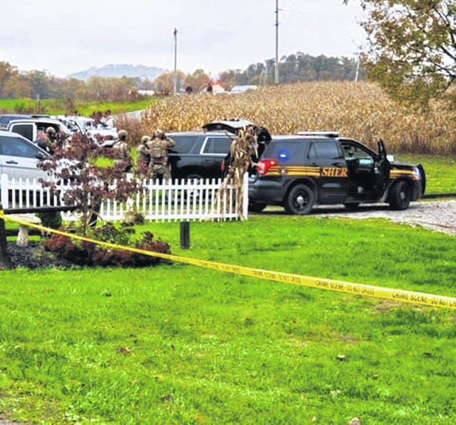Officers are pictured outside Monday in Cynthiana near a residence where Patrick Stuart Jackson was taken into custody.