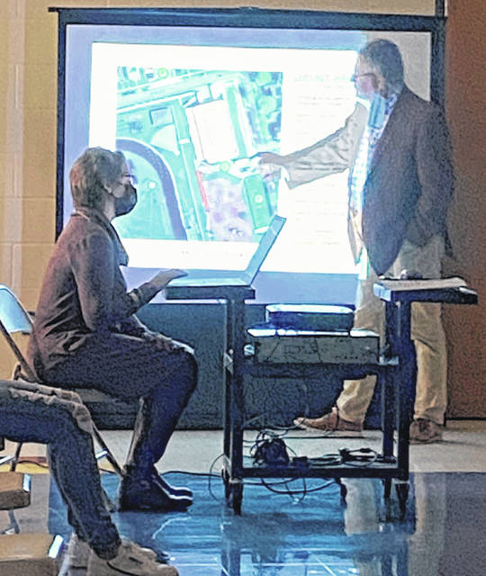 Architect Doug Karnes is pictured at Monday's Greenfield School Board meeting discussing conceptual plans for development in the district. Superintendent Quincey Gray (seated) is also pictured.