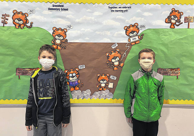 Third grader Jodei Rickman and fifth-grader Bryce Barber are pictured with a bulletin board demonstrating the process of facing a challenge and working through it.