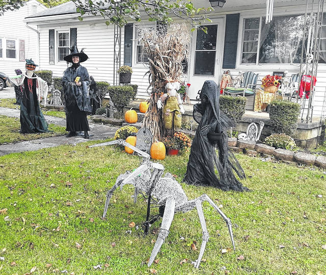 Joan Murphy is pictured in her Halloween garb as she stands in her decorated yard at 527 Edgewood Ave. She is holding the plaque she was awarded by the village of Greenfield for having the best decorated home for Halloween.