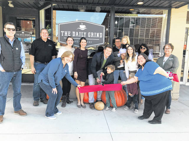 The Daily Grind Cafe and Bakery and Downtown Drug owner Dane Allard (center, holding scissors) celebrates the cafe's grand reopening with a ribbon-cutting ceremony.