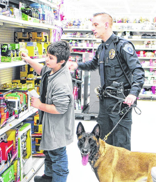 """In a scene from a previous """"Shop with a Cop"""" event, Aiyden Norris-Feltner, left, selects a toy tractor at the Hillsboro Walmart with Officer Adam Day of the Hillsboro Police Department. Also shown is the department's police canine, Harley."""