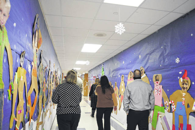 "Lynchburg-Clay Elementary School Principal Angela Godby takes board of education members on a tour throughout the elementary building, which students and staff decorated for the school's hallway decorating contest. The second-grade hallway, pictured, won the contest with its ""Gingerbread Lane"" hallway."