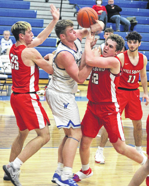 Washington High School sophomore Tanner Lemaster battles Hillsboro senior Coltin Hunter for possession during a Frontier Athletic Conference game Tuesday at Washington C.H. Also pictured for the Indians are senior Hunter Price (25) and senior Ryan Scott (11).