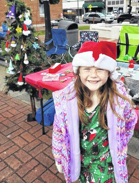 Seven-year-old Paisley Flora is pictured in front of the booth she set up last weekend at the Greene Countrie Towne Holiday Fest in Greenfield.