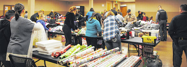 In a scene from last year's Shop with a Cop event, 17 Highland County children end a day of festivities by wrapping the gifts they bought earlier in the day.