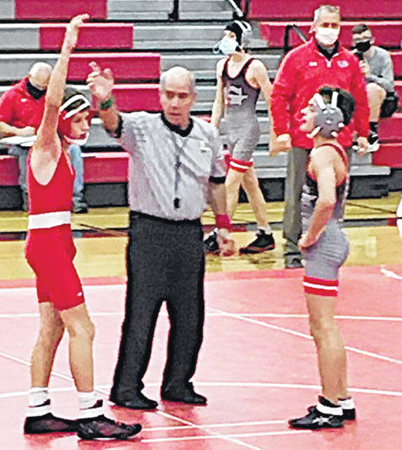 Matthias Hostettler has his arm raised in victory after pinning a Goshen opponent.