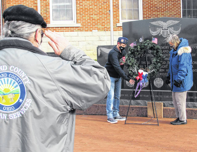 Following a moment of silence, members of the Highland County Veterans Honor Guard, Daughters of the American Revolution and the Highland County Veterans Services Office participated in a wreath-laying ceremony Saturday morning at the veterans memorial on the Highland County courthouse square. Honor Guard veteran Gerold Wilkin rendered a military salute as, shown from left, veterans service office outreach coordinator Steph Roland and Pat Young of the local DAR formally laid the wreath as part of the national Wreaths Across America observance. According to Wilkin, Wreaths Across America has a three-fold purpose: to remember the fallen U.S. veterans, to honor those who serve, and to teach children the value of freedom.