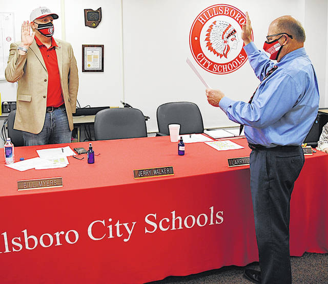 Bill Myers (left) is sworn in Monday for another term as Hillsboro Board of Education president by treasurer Ben Teeters.