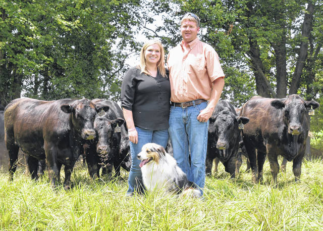 Lindsay and Adam Hall are pictured with cattle at Maplecrest Farms south of Hillsboro on SR 73.