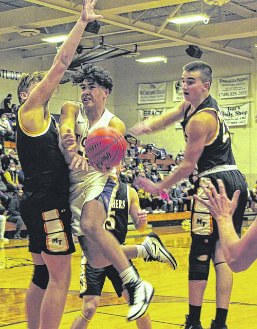 McClain junior Kendyll Toney takes the ball to the basket against Miami Trace sophomores Andrew Guthrie (left) and Isaiah Reisinger.