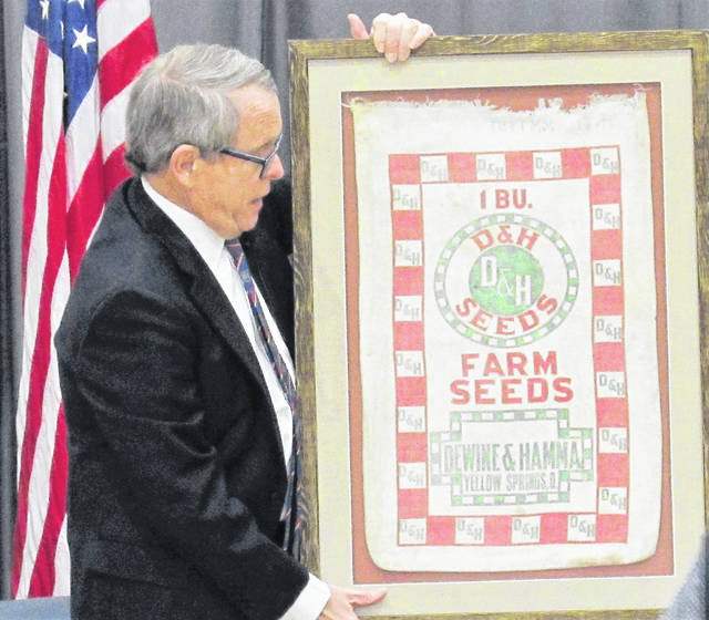 Acting as the keynote speaker at last year's Ag Is Everyone's Business event in Hillsboro, Ohio Gov. Mike DeWine holds a specially framed 1955 seed bag from his family's seed business in Yellow Springs. The bag was a gift from the Highland County Chamber of Commerce.