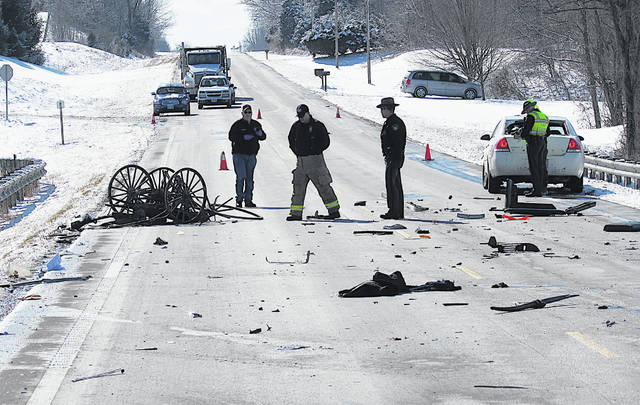 Emergency personnel look over the remains of what turned out to be a fatal crash involving an Amish buggy Tuesday on U.S. Route 62 just south of New Market.