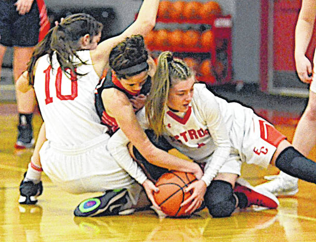 Fairfield's Peyton Magee battles two East Clinton Lady Astros for a loose ball during Saturday's non-league game.