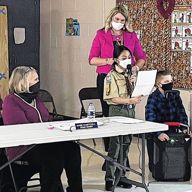 Rainsboro Principal Maggie Lyons stands behind students Leina Grace, left, and Cale Flowers, right, as they help present information to the school board about learning dispositions.
