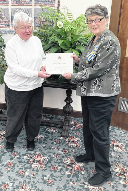 Rosemary Ryan (left) receives her 10-year Waw-wil-a-way Chapter of the Daughters of the American Revolution membership certificate from Regent Jane Stowers.
