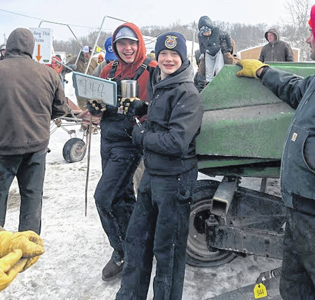 Hillsboro FFA members Bryce Parsons (left) and Brogen Priest are pictured holding up auction numbers at the annual alumni consignment auction.