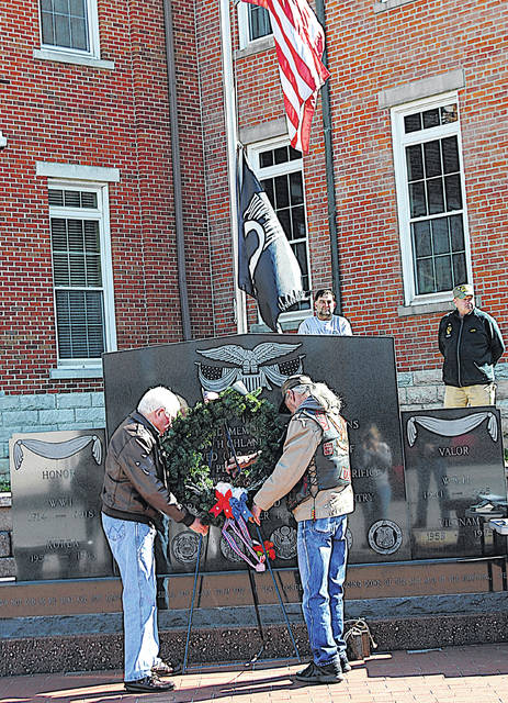 Local Vietnam War veterans Ron Sampson (left) and Frank Terwilliger place a wreath Monday in front of the Veterans Memorial at the Highland County Courthouse on Vietnam Veterans Day.