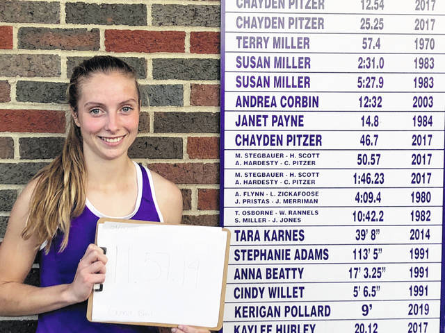 Gene've Baril is pictured next to the McClain High School track and field records board where her name will soon be placed.