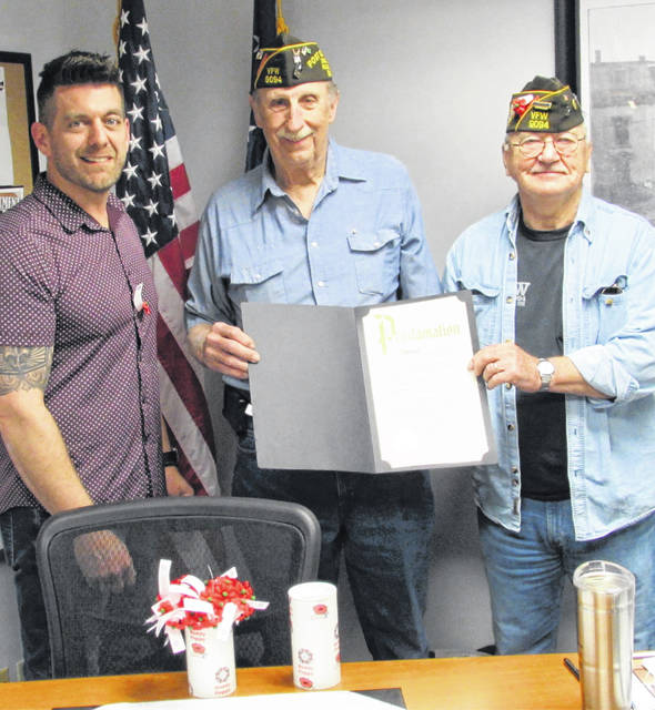 """Recognizing the Buddy Poppy creed of the VFW, """"Honor the Dead by Helping the Living,"""" Hillsboro Mayor Justin Harsha on Monday proclaimed the month of May as Buddy Poppy Month in Hillsboro. Recognized and endorsed by government leaders since 1922, VFW Buddy Poppies are assembled by disabled veterans, with Senior Vice Commander Dwight Reynolds adding that all proceeds from Buddy Poppy sales remain in the local community. Hillsboro VFW Post 9094 Commander Rick Wilkin said that during this year's Memorial Day observance at the Veterans Memorial in Hillsboro, two local veterans of the 1944 Battle of the Bulge will be honored, and that if there were any other locals veterans of what British Prime Minister Winston Churchill called """"the greatest American battle of the war,"""" to contact the post at 937-393-0211 and leave a message. Wilkin said that the most new bricks in recent years will be enshrined at the Veterans Memorial, with Reynolds adding that two were replacements, but 37 were new ones that will be installed honoring veterans past and present, living and deceased. Shown (l-r) are Harsha, Wilkin and Reynolds."""