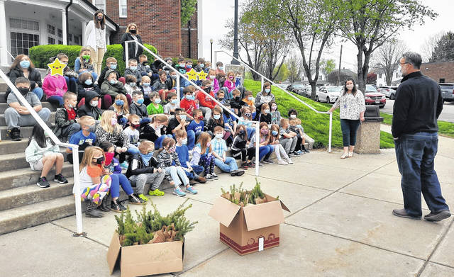 First grade students, along with their teachers, at Greenfield Elementary are pictured as they heard from Greenfield City Manager Todd Wilkin about trees, which is part of the village's annual observance of Arbor Day. Waiting in the boxes in the foreground are the spruce seedlings each child gets to take home to plant. Note: A star sticker has been placed to protect the identity of certain students.