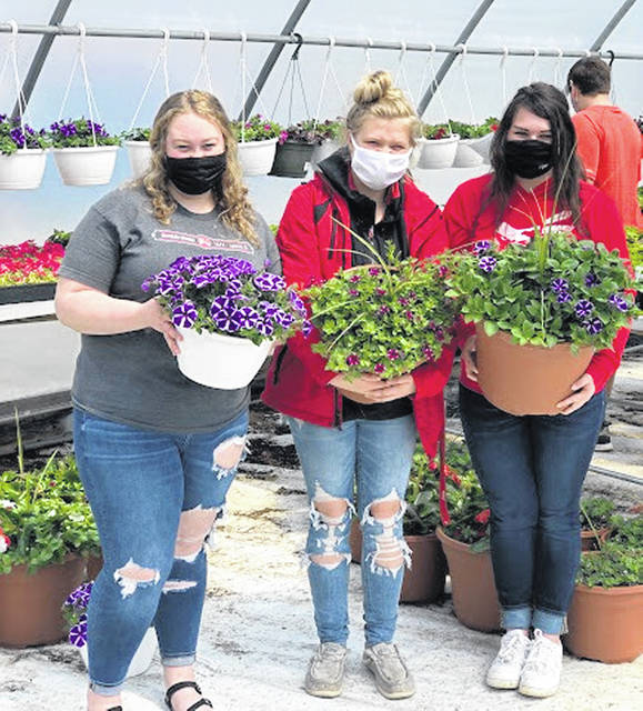 Emma Hatfield, Madison Curtis and Clara Page show some of the greenhouses options for the Hillsboro FFA Spring Flower Sale.