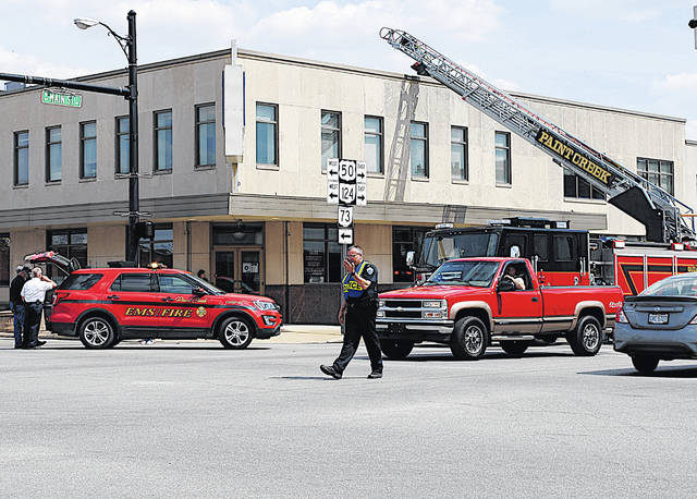 Hillsboro Police Chief Eric Daniels directs traffic Tuesday afternoon in the center of Hillsboro after the Paint Creek Joint EMS/Fire District was called to Merchants National Bank at 12:50 p.m. Paint Creek Lt. Branden Jackman said an HVAC unit on top of the building had shorted electrical wires and a ceiling joist was slightly charred. He said the incident caused a slight haze in the upper level of the building. The event slowed traffic in the center town for about two hours. Paint Creek cleared the scene at 2:55 p.m.
