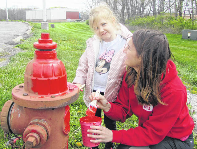"""Alison Lyle and her daughter, 4-year old Maren, are shown giving a new coat of paint to one of the fire hydrants at the Highland County Justice Center last Friday. Lyle said it was part of Good News Gathering's """"Big Give Weekend,"""" a community ministry outreach program of the church to the city of Hillsboro. She said others in the congregation, in addition to scraping and painting fire hydrants, were involved in mowing grass in the community and doing general clean-up at Shaffer Park."""