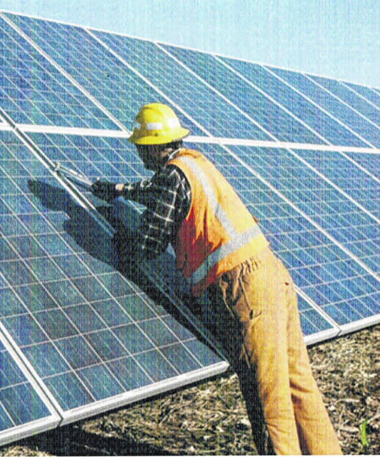 A technician is shown working on one of National Grid Renewables' many solar panel projects across the country.