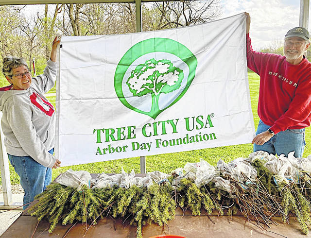 Greenfield Tree Commission members Holly Ellinger (left) and Ron Coffey hold a Tree City USA banner and display some of the seedlings that will be given away on Friday, April 30 at the Greenfield City Building.