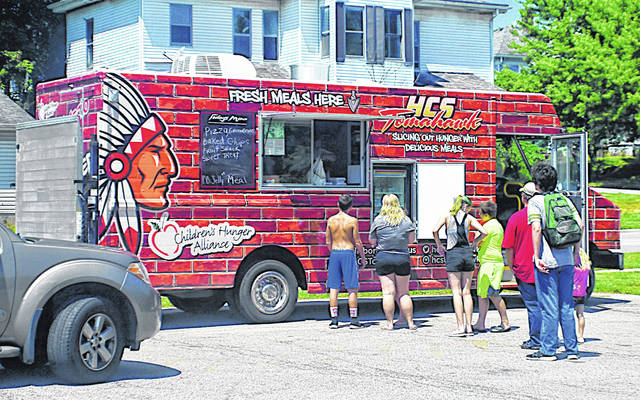 Staff with the Hillsboro City Schools Tomahawk Food Truck deliver meals during a past summer stop in Hillsboro.