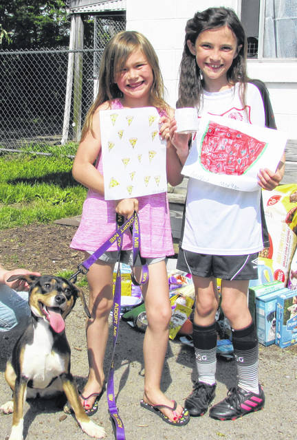Shown at the Humane Society Animal Shelter are Hazel, a dog that newly-adopted, Kennedy Horne (left) and Adelyn Morgan, who sold their original drawings to benefit the Humane Society.