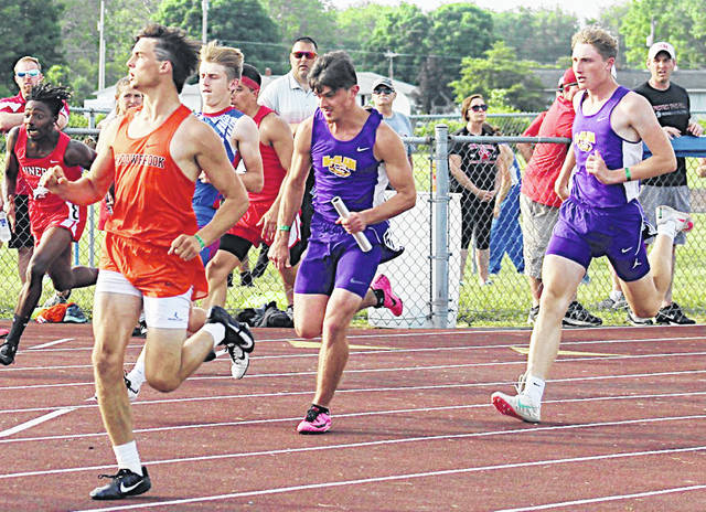 In the McClain boys 4 x 100-meter relay Seth Wise hands off to Matt Bliss.