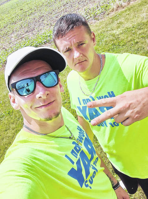 Chris Clark (left) and Cody Wright were among the individuals who volunteered at a community event in Washington C.H. in which mattresses, microwaves, clothes and food were given out to more than 400 people in attendance.