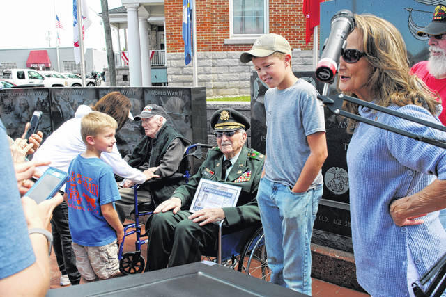 Hillsboro Memorial Day guests of honor Herman Holt (left) and Mac McCray, 101 and 98 respectively, receive congratulations following an observance Monday at the Highland County Veterans Memorial. Both men served in the Battle of the Bulge.
