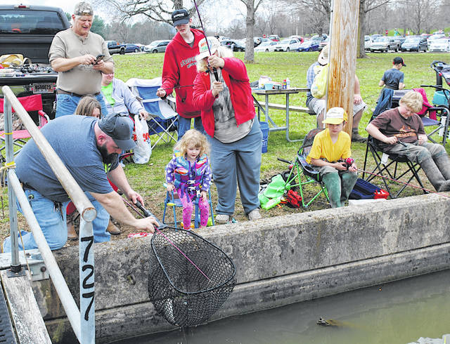 Hillsboro resident Anthony Garretson (left) helps 3-year-old Violet Nihart of Wilmington net a trout she reeled in during the 2019 Highland County Rod & Gun Club's annual Trout Derby at Rocky Fork Lake.
