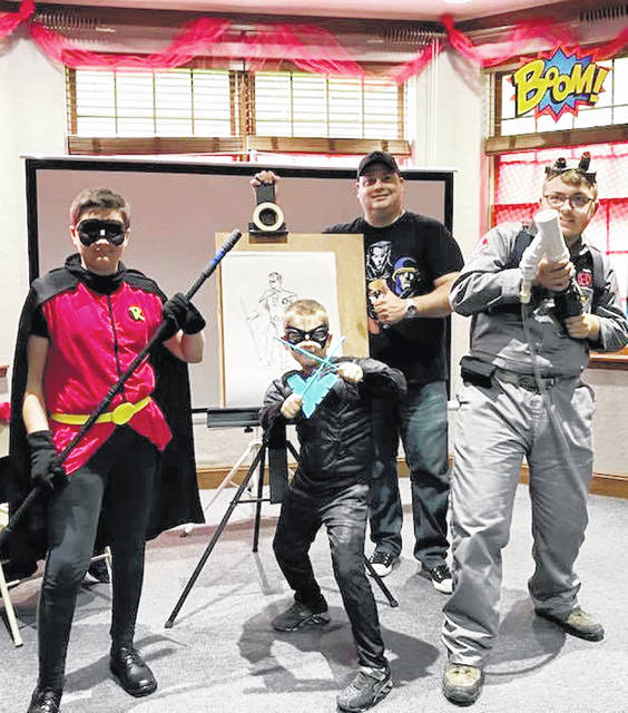 Pictured above are three costumed con-goers and guest artist William Roller at a previous Library Comic Con.